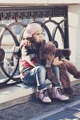 foto of beret  - little girl in a pink beret sits at a fencing and holds a toy bear in hand - JPG