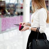 picture of payday  - Young stylish woman in cute trendy outfit with leather handbag looking into purse - JPG