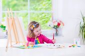 picture of little school girl  - Cute happy little girl adorable preschooler painting with water color on canvas standing on a wooden easel in a sunny white room at home or elementary school creative young artist at work - JPG