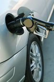 picture of fuel pump  - A fuel pump filling the gas tank of a silver car - JPG