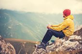 stock photo of cliffs  - Man Traveler relaxing alone in Mountains Travel Lifestyle concept cloudy nature landscape on background - JPG