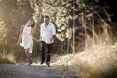 picture of flirtatious  - happy flirtatious Indian couple walking along dirt road together - JPG