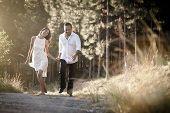 image of flirtatious  - happy flirtatious Indian couple walking along dirt road together - JPG