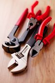 stock photo of claw  - Closeup adjustable wrench pliers claw hammer and pliers on the wooden background - JPG