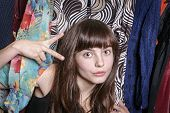 foto of thrift store  - teenage girl with her wardrobe showing a scissors with one hand - JPG