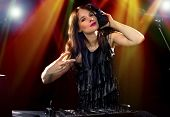 pic of emcee  - caucasian female dj using a mixer and computer to play mp3s - JPG