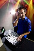 stock photo of emcee  - caucasian male dj playing mp3 music with computer and mixer - JPG
