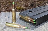 stock photo of ammo  - Magazine on wood planks with green tipped metal ammo - JPG