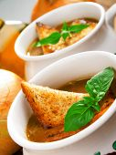 stock photo of onion  - Famous onion soup with onions and olive oil in the background close up - JPG