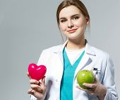 pic of cardiology  - Beautiful smiling female doctor holding red heart and green apple in front of chest - JPG