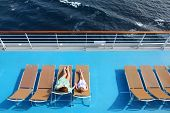 Mother And Daughter Lying On Beach Armchairs On Cruise Liner