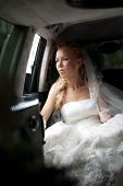 Bride in wedding dress sits in limousine and looks out in window.