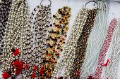 picture of beads  - Display of variety of colorful white and transparent beaded necklaces - JPG