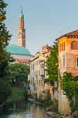 stock photo of vicenza  - Retrone river in Vicenza with some old houses at its bank and the medieval clock tower seen from Furo bridge before the sunset - JPG