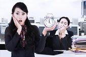stock photo of yawn  - Portrait of businesswoman holding alarm clock and her friend looks yawning on the back - JPG