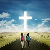 pic of rear-end  - Back view of female students walking on the highway toward a cross on the end of the road - JPG