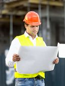 image of scaffold  - Portrait of foreman reading blueprints against scaffolding at building site - JPG