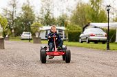 picture of buggy  - Young white boy driving on buggy cart at camping site on cloudy day - JPG