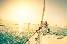 stock photo of sailing vessels  - Young couple in love on sail boat with champagne at sunset  - JPG