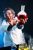 Mad Scientist extending explosive concoction away from his face