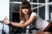 The young charming girl in a sports hall on a velosimulator