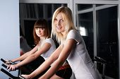Two charming girls in a sports hall on velosimulators