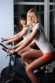 foto of muscle man  - Two charming girls in a sports hall on velosimulators - JPG