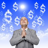 praying business man against dollar background