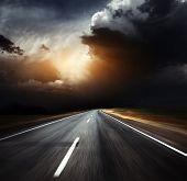 Blurred asphalt road and dark thunder clouds over it