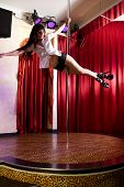 stock photo of strip-tease  - Strip tease dancer hanging on the pole in stripclub - JPG