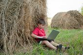 A Boy With A Laptop In The Field