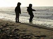 Silhouette Of Two Children Playing Along The High Tide Line