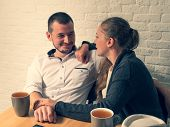 The Girl And The Guy In Cafe, At A Table, Talk. The Guy And The Girl With Love And Tenderness Look A poster