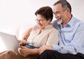 stock photo of elderly couple  - Senior couple on laptop - JPG