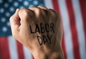 closeup of the raised fist of a young man with the text labor day handwritten in it, and the flag of poster