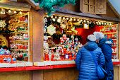Постер, плакат: People At The Stall On Christmas Market At Kaiser Wilhelm Memorial Church In Winter Berlin Germany