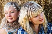Two Country Girls On Straw Bales Background.