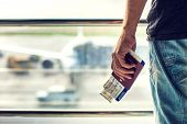 Closeup Of Man Holding Passports And Boarding Pass At Airport. Traveling Concept poster