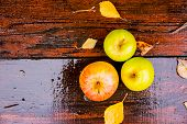 Three Wet Golden Green Apples Covered By Water Drops On Top Of Brown Wet Natural Old Wooden Table Su poster