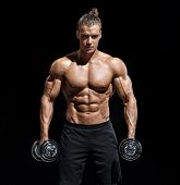 Powerful Man Doing The Exercises With Dumbbells. Photo Of Young Man With Good Physique On Black Back poster