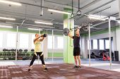sport, fitness, weightlifting, lifestyle and people concept - man and woman with kettlebell and barb poster