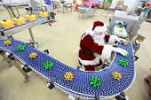 santa claus as a quality control manager at christmas ornament production line in factory