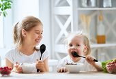Two children having breakfast. Kids eating cereal and berry in kitchen. poster