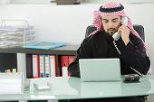 Retrato de un hombre de negocios árabe inteligente usando laptop y hablar por teléfono