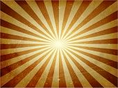 Abstract vintage background with light burst in golden brown. Grunge elements give it a textured and aged feeling.