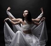 Portrait of two girls in white raiment dancing in semidarkness