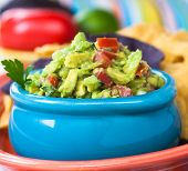 stock photo of nachos  - Tasty guacamole bowl with chips and fresh ingredients on the side.