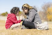 stock photo of glorify  - Single mother teaching her son and glorifying God through prayer - JPG