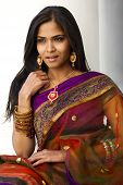 stock photo of traditional attire  - A portrait of a young 20 something Indian woman with long black hair dressed in purple and gold traditional Indian attire  - JPG