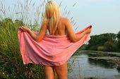 foto of partially nude  - Sensual image of a young female partially nude covered with a bath towel - JPG